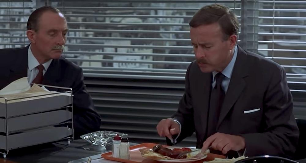 Ο αστυνόμος τρώει πρωινό, ενώ ο αρχιφύλακας τον παρακολουθεί.